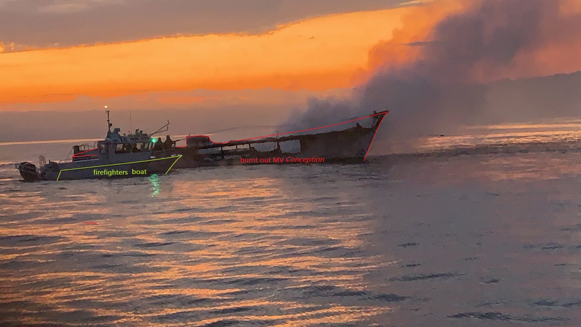 burnt out dive trip boat MV Conception and firefighters on another boat behind it.jpg